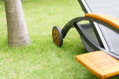 metal chaise-longue on green grass near tree. - stock photo