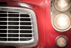 Close up of grille and headlights of red vehicle Stock Photos
