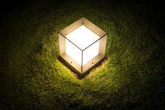 lighting cube lantern on grass at night. - stock photo