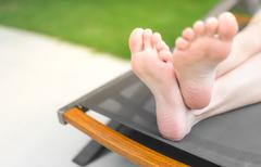 Feet and soles of person lying on sunbed. Stock Photos