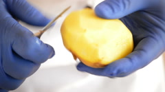 Hands of professional chef peeling potatoes detail Stock Footage