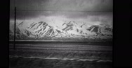 View of snowcapped mountains from train while goods being transported Stock Footage