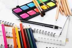 albums with water colour paints and pencils - stock photo