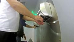 4k man dry hands on modern hand dryer in toilet Stock Footage