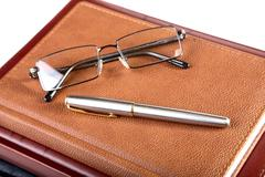 Organizer glasses and fountain pen Stock Photos