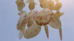 Mobile Shell hanging on the sky background and glowing sunlight. HD. 1920x1080 Stock Footage