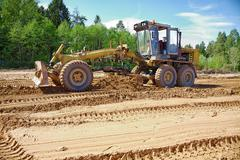 the grader clears away a ground in the afternoon - stock photo