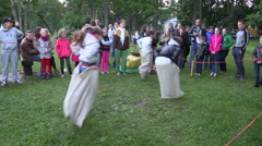 Active children play sack race in city park with people audience Stock Footage