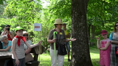 Panorama of botanical garden guide tell stories to tourist group Stock Footage