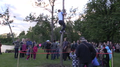 Stock Video Footage of Young man climb on high log pole to get hanging prize