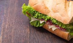 sandwiches - turkey breast, ham & swiss and salami on old cutting board. - stock photo