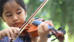 Little Asian girl  playing violin in the park - stock footage