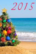 christmas tree on the sand in the beach - stock illustration
