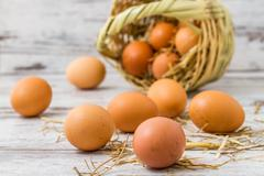 Natural brown eggs fallen from a straw basket on white wooden background Stock Photos