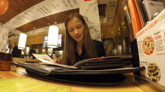The girl is studying in the menu Japanese restaurant Stock Footage