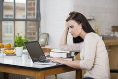 Harassed young woman working on a laptop Stock Photos