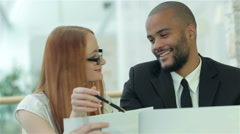 Smiling successful businessmen sitting at table in office while discussing Stock Footage