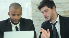 Two young men discussing information on the laptop screen - stock footage