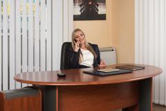 businesswoman talking on telephone in office - stock photo