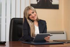 businesswoman talking on telephone and using computer - stock photo