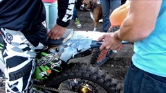 FMX riders examining motorcycle dammage, 2 scenes Stock Footage