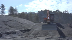 An excavator moving shingle Stock Footage