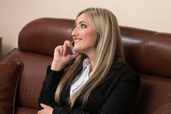 Businesswoman talking on telephone in office Stock Photos