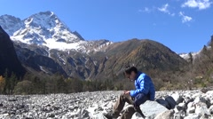 Hiker taking a rest and playing smartphone games, snow mountains in the backgrou Stock Footage
