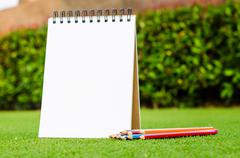 Color pencil and sketchbook on fresh spring green grass Stock Photos