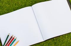 color pencil and sketchbook on fresh spring green grass - stock photo