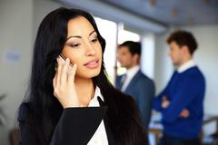 Stock Photo of serious businesswoman talking on the phone with colleagues on background