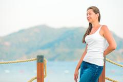 Beautiful girl on the pier looks attentively aside Stock Photos