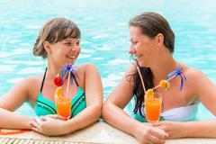 two friends laughing and joking in the pool - stock photo