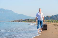 stroll along the sandy beach with luggage - stock photo