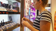 Young Beautiful Woman Chooses Mascara at Cosmetics Shop. Stock Footage