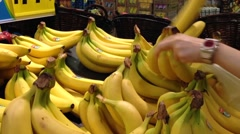 Woman selecting banana in grocery store Stock Footage