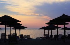 Sunset on the beach of Aegean Sea. - stock photo