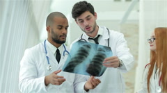 Three confident doctor examining x-ray snapshot of lungs in hospital - stock footage