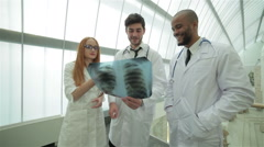 Three confident doctor examining x-ray snapshot of lungs Stock Footage