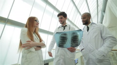 Three confident doctor examining x-ray snapshot of lungs - stock footage
