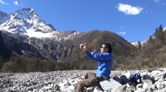 Hiker taking photo with cell phone in the snow mountain area Stock Footage