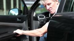 Senior driver looking at camera, closing car door and driving away Stock Footage