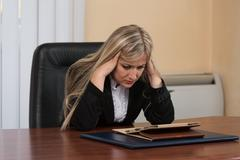 Overworked businesswoman sitting by her desk Stock Photos