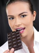 Attractive woman biting into a bar of chocolate Stock Photos