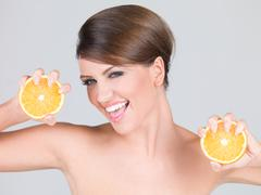 Vivacious playful woman with fresh orange slices Stock Photos