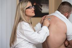 Listening back of patient with stethoscope Stock Photos
