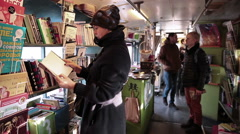 Visitors read books in the bookstore on wheels. Stock Footage