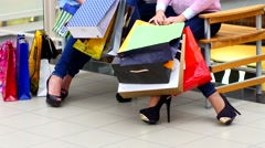 Two beautiful girls with shopping bags watch purchase on shopping center - stock footage