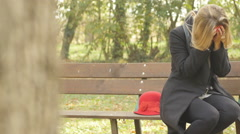 Desperate woman sitting on a bench outdoor crying steady cam uhd 4k Stock Footage