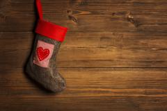 christmas stocking, sock hanging over grunge wooden background, brown wood - stock photo